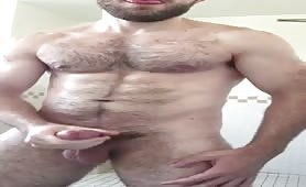 Handsome hairy stud stroking his tatsy long cock solo