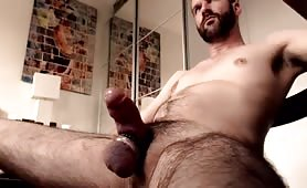 Hairy stud stroking his fat meaty cock
