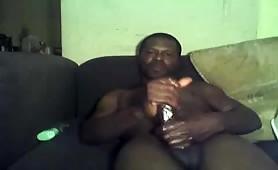 Horny black dad stroking his beefy fat cock solo on his sofa